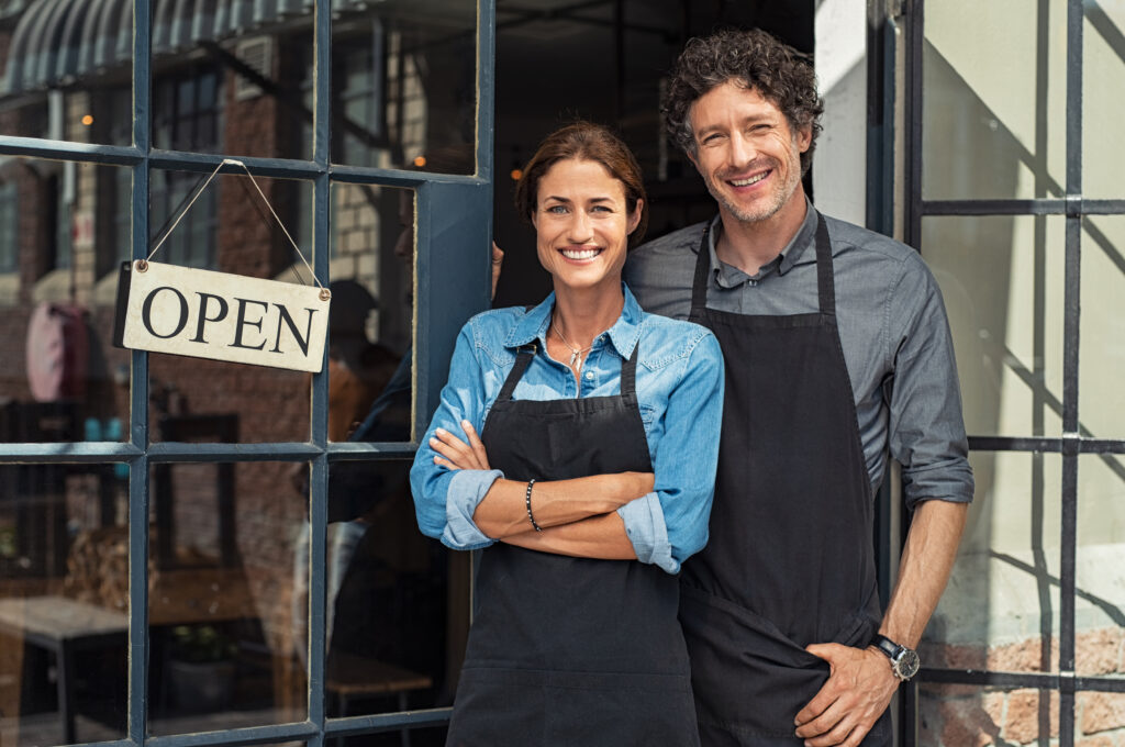 shop local two people standing in doorway by open sign