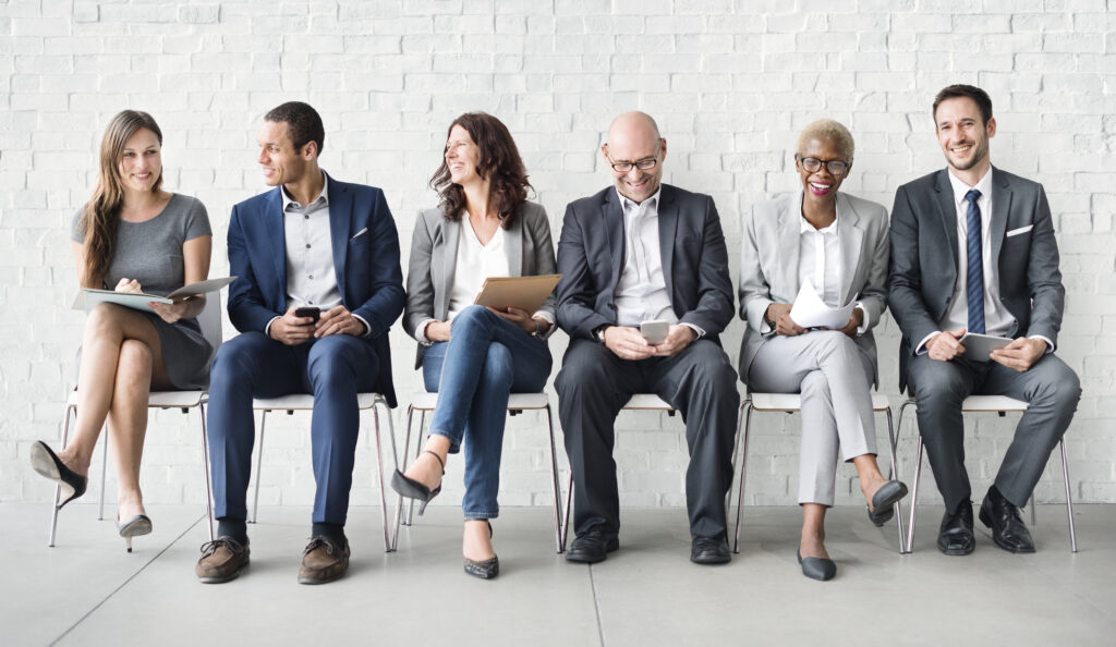 line of business people sitting in chairs against brick wall