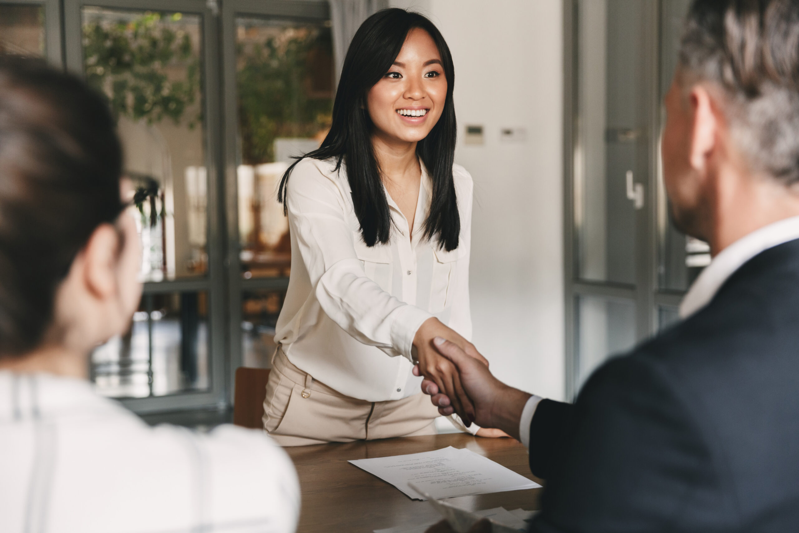 young woman shaking hand with business man at job interview