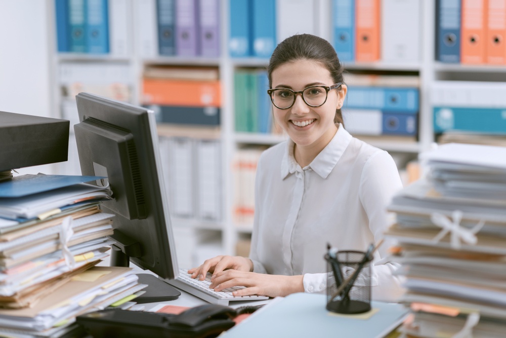 female office administrator sitting at desk at work