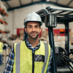 forklift operator in warehouse man wearing yellow hard hat and safety vest at job