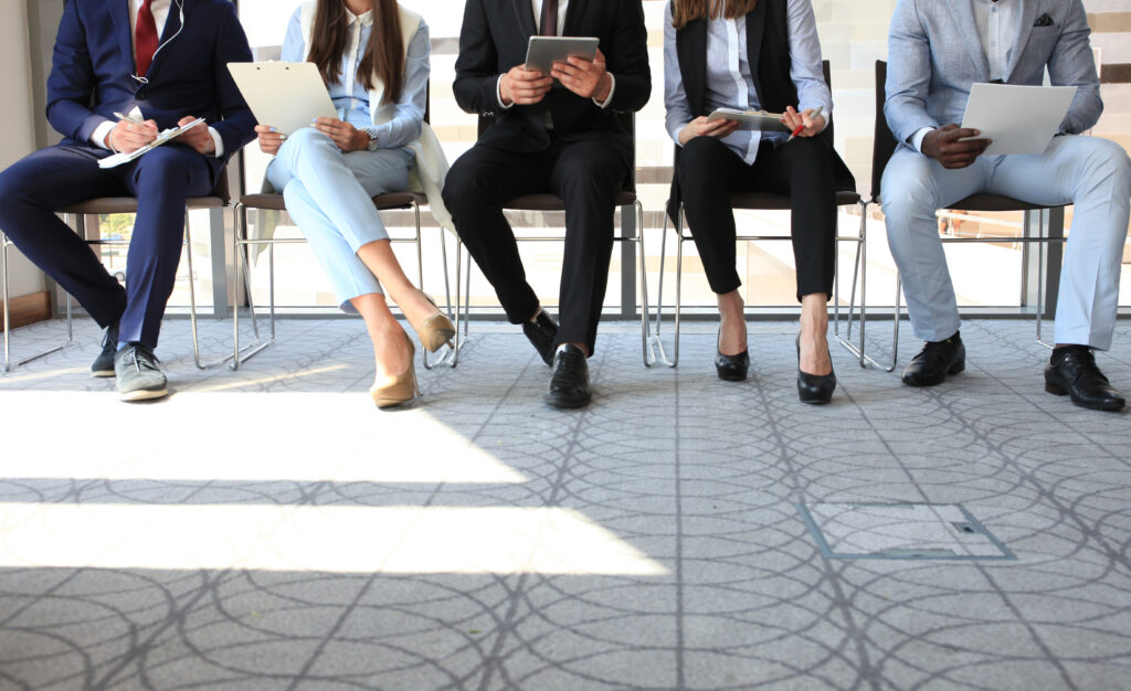 picture of a line of business people sitting in chairs and all you can see is their feet waiting for interview