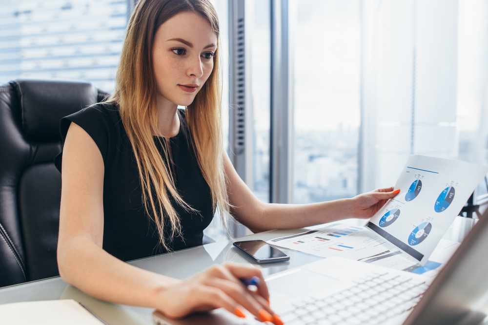 female financial analyst at desk at work