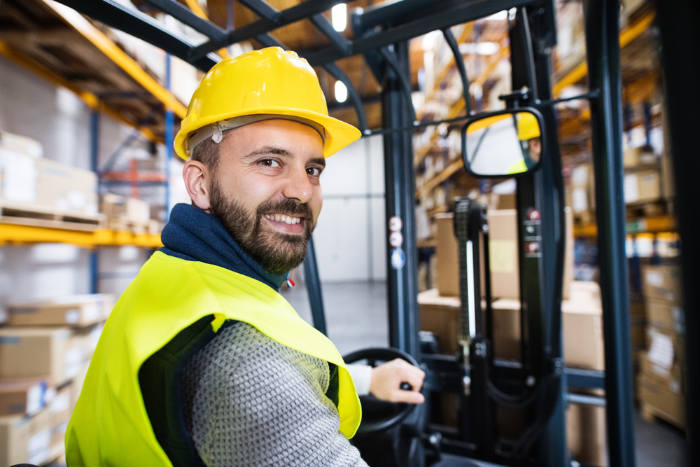 forklift operator man in yellow hard hat in factory warehouse
